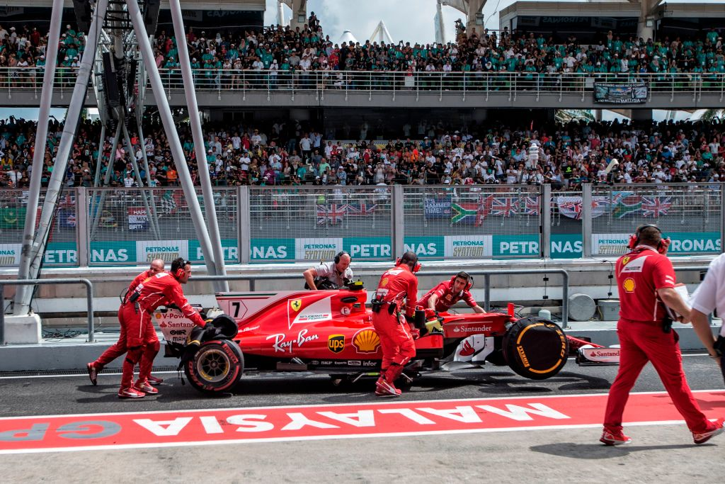 Team members push Ferrari's Finland driver Kimi Raikkonen's car into the garage during the Formula One Malaysia Grand Prix in Sepang on October 1, 2017. / AFP PHOTO / POOL / AHMAD YUSNI        (Photo credit should read AHMAD YUSNI/AFP/Getty Images)