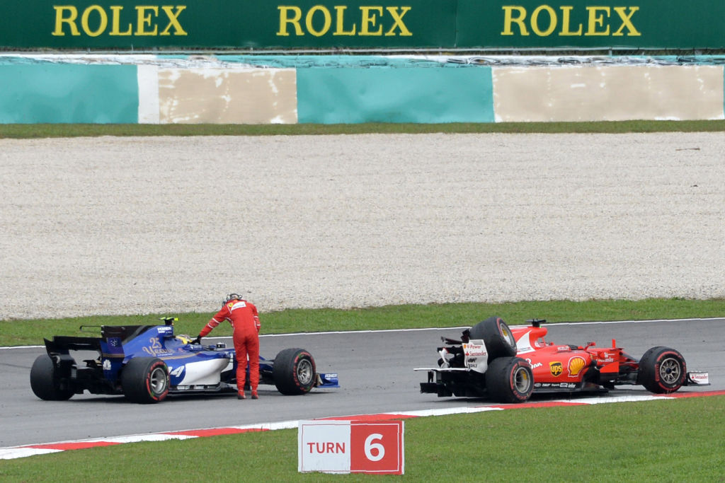 Ferrari's German driver Sebastian Vettel is given a ride by Sauber's German driver Pascal Wehrlein after he crashed past the chequered flag during the Formula One Malaysia Grand Prix in Sepang on October 1, 2017.   / AFP PHOTO / ROSLAN RAHMAN        (Photo credit should read ROSLAN RAHMAN/AFP/Getty Images)
