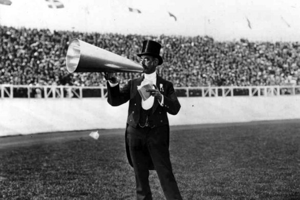 The master of ceremonies using a megaphone - Topical Press Agency/Getty Images