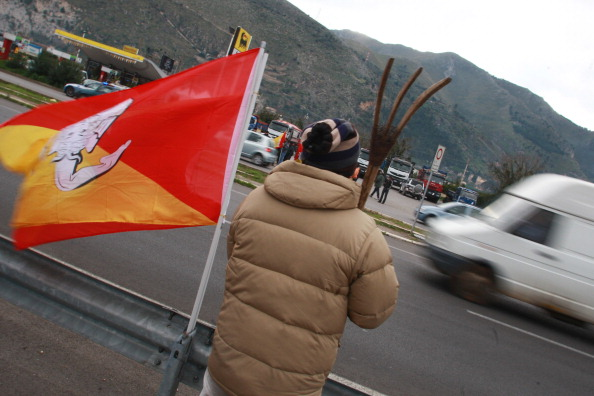 A protester holds a pitchfork as truck d