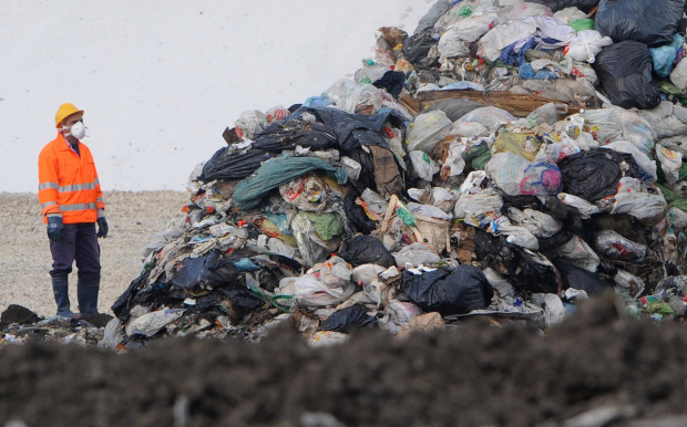 A dump employee looks at rubbish from th