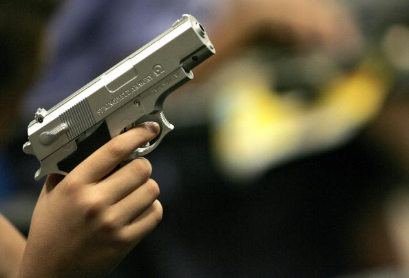 A child holds a fake plastic gun during