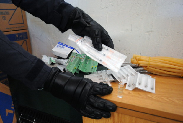 Policemen search in boxes of syringes in