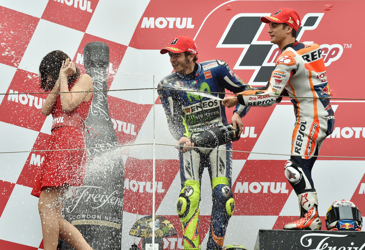 Winner Repsol Honda Team rider Dani Pedrosa of Spain (R) celebrates his victory on the podium by spraying champagne next to second-placed Movistar Yamaha MotoGP rider Valentino Rossi of Italy (C) during the awards ceremony at the MotoGP Japanese Grand Prix in Motegi, Tochigi prefecture on October 11, 2015.     AFP PHOTO / KAZUHIRO NOGI        (Photo credit should read KAZUHIRO NOGI/AFP/Getty Images)