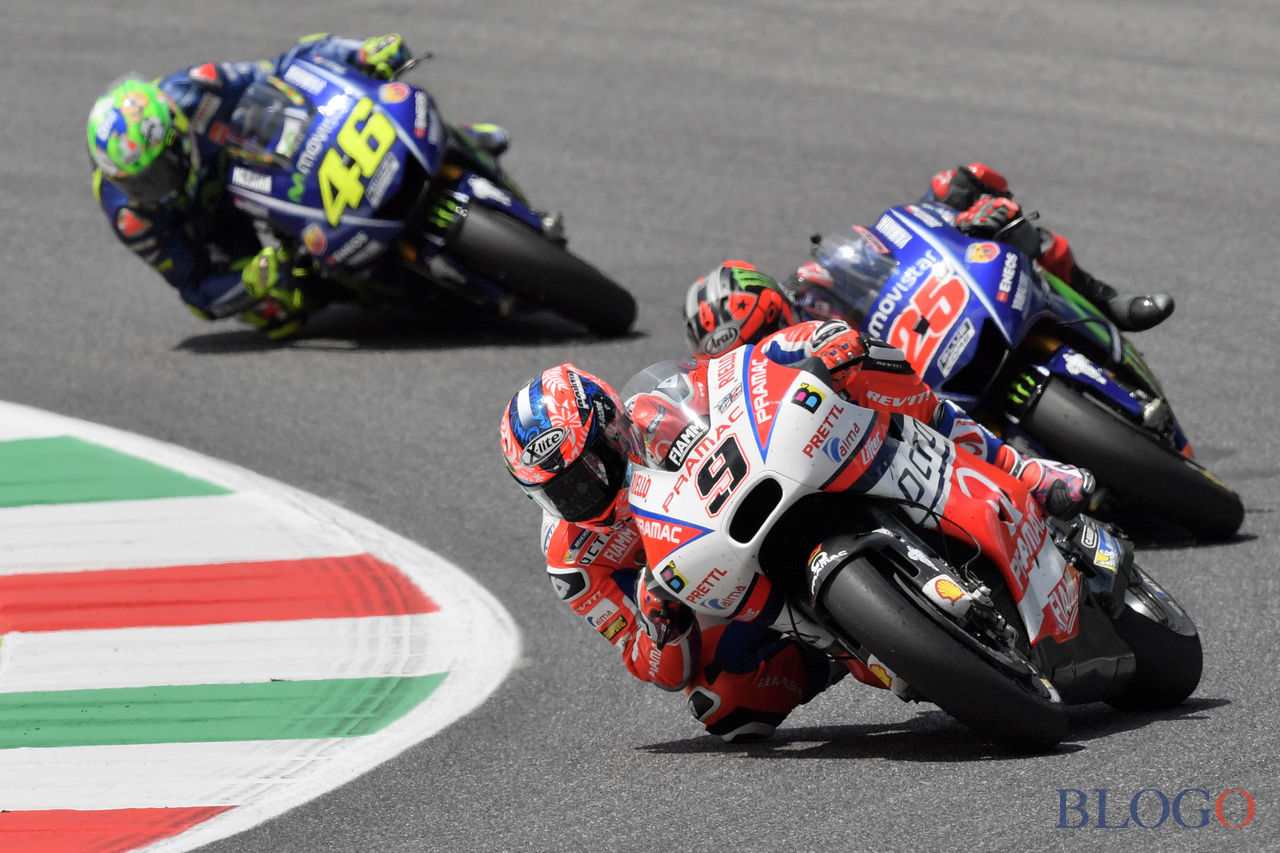 OCTO Pramac Yakhnich's Italian rider Danilo Petrucci competes ahead of Movistar Yamaha's Spanish rider Maverick Vinales (R) and Movistar Yamaha's Italian rider Valentino Rossi (L) during the Moto GP Grand Prix at the Mugello race track on June 4, 2017.  Ducati's Andrea Dovizioso thrilled the home crowds with a stirring MotoGP victory at Mugello on Sunday that saw him edge championship leader Maverick Vinales. Another Italian, Danilo Petrucci, was third while veteran superstar Valentino Rossi of Yamaha won plaudits for racing in pain from a training accident and finishing fourth having set the early pace.  / AFP PHOTO / Tiziana FABI        (Photo credit should read TIZIANA FABI/AFP/Getty Images)