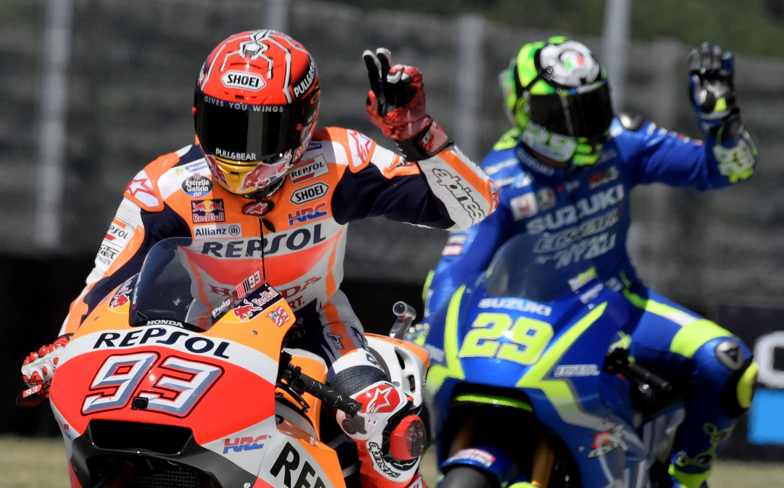 Repsol Honda rider Spanish Marc Marquez (L) and Suzuki Ecstar rider Italian Andrea Iannone wave during the Moto GP free practice session of the Italian Grand Prix at the Mugello track on June 2, 2017. Seven-time world MotoGP champion Rossi is struggling with chest pains after a motocross training accident that saw him hospitalised last week.  / AFP PHOTO / TIZIANA FABI        (Photo credit should read TIZIANA FABI/AFP/Getty Images)
