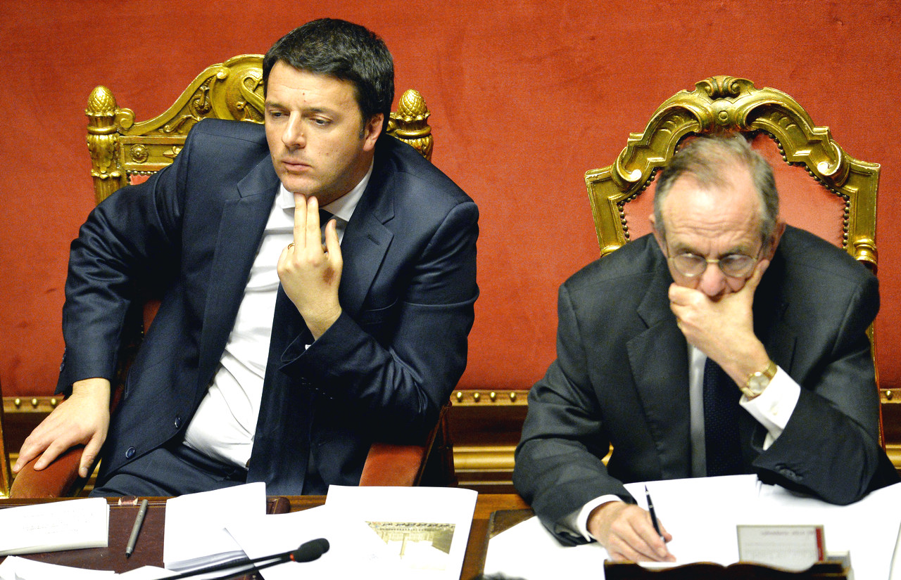 Newly appointed Italian Prime Minister Matteo Renzi (L) looks on, alongside Italian Economy and Finance Minister Pier Carlo Padoan, during a debate ahead of a confidence vote at the Italian Senate on February 24, 2014, in Rome. Italy's new Prime Minister Matteo Renzi was to unveil details of his ambitious government programme on February 24 as he faced a confidence vote in parliament in a key test of his power to unite warring factions and secure a solid majority. The new premier is expected to present plans for rapidly overhauling the tax system, job market and public administration in his speech to the Senate, which will put his newly-formed cabinet to a confidence vote. AFP PHOTO / ANDREAS SOLARO        (Photo credit should read ANDREAS SOLARO/AFP/Getty Images)